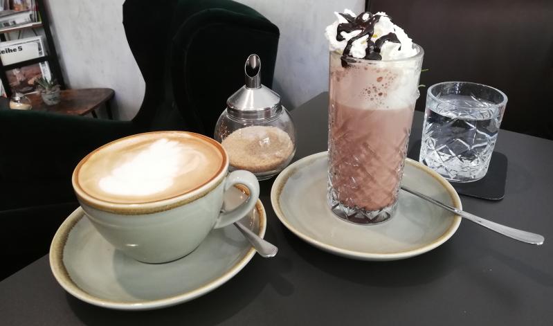 Kaffeespezialitäten werden im Café & Bar deer mit einem Glas Wasser serviert.